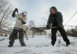 Neil Shegoner (cq), left, and Duck Schran (cq) work on removing ice from a sidewalk in front of...
