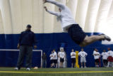DM1121   Coach Ernesto Purnsley watches as Ryan Clement leaps in the broad jump during the tryouts...