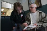 Kathie Reinhardt (cq) helps 37-year-old Michael Morrone (cq) fill out his paperwork at the St....