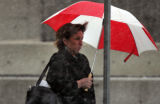 Teresa Sedmak (CQ), shields herself with an umbrella as she waits for her bus at the corner of...