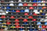 Baseball caps are lined up by style and size on the wall at Young Sports Mart at 270 S. Federal...