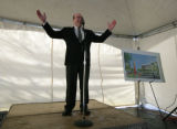 Aurora Mayor Ed Tauer stands by a drawing of a new development -Gardens of Aurora -at the site of...