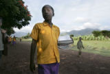 With his uniform and school books, Nuri walks to school at the Project Mercy compound from his...