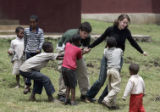 Abe Ritter, center, and Lauren Tatarsky, right, play with the kids at the Project Mercy Compound....