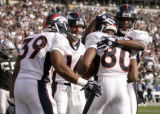 Denver Bronco wide receiver Rod Smith (#85 back to frame) is congratulated by teammates, left to...