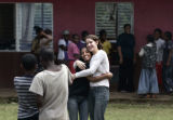 Meron Abebe and Lauren Tatarsky, center, hug while being videotaped by two of the children that...