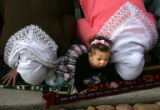 Yasmin Kemeha (cq), 6 months, of Denver, lies on a blanket while her mother, Safiyyah Kemeha (cq),...