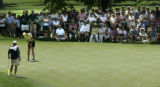 On 6th green Michelle Wie putts as she is  surrounded by her fans. He caddie Jimmy Johnston stands...