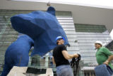 Denver artist Lawrence Argent (cq, left) laughs as the head to the bear is lifted into the air...