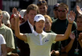 Birdie Kim, of Korea, waves to her fans after claiming her trophy on the 18th green after...