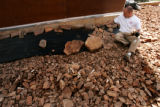 HGTV DREAM HOUSE.  Christopher Herr (cq) puts rocks over weed barrier on a 3-foot perimeter around...