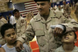 SPC Johnny Escoto uses his son Emilio Escoto's, 8, head as an arm rest for his sore hand while his...