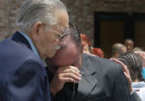 Anthony Martinez(cq), right, cries with his great grandfather Orlando Martinez Sr. (cq) after the...