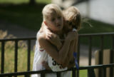 Remington, right, hugs her younger sister Remington, left, after they completed the 5K family fun...