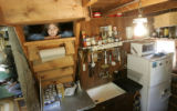 Ana Fairbanks-Mahnke, cq, 7, peeks through a cubby hole in the rustic kitchen of a cabin believed...