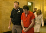 (Center) Brent Brents, who plead guilty to 66 felony charges, was escorted out of Judge Robert...
