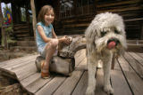 Ana Fairbanks-Mahnke, cq, 7, plays with her dog Casper on the rustic porch of a cabin believed to...