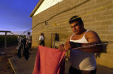 An unidentified migrant worker does his laundry after a 12-hour long day in the fields outside of...