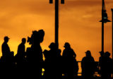 The Colorado Rockies masscott, Dinger, makes his way through a crowd as the sun sets on Wednesday...