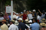The gallery crowds No. 5 to watch teenager Michelle Wie, of Hawai, as she follows through on  her...
