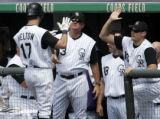 Colorado Rockies' #17, Todd Helton, left, is congradulated by manager,#13, Clint Hurdle, center,...