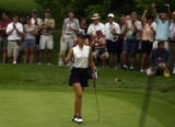 15-year-old golf phenom, Michelle Wie (left) is cheered on by her mother and fahter (right top...