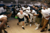 Broncos players cheer on assistant strength coach Greg Saporta at the Arapahoe Bowling Center in...