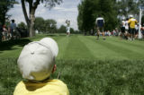 Trevor Zick (cq), 5, watches Birdie Kim tee off on the 5th hole on the second day of competition...