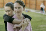 Vera Chatwin, left, 13, hugs her mom, Lori, in their front yard at their home in Colorado City,...
