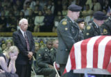 Riley Vasquez, left, wife of SSG Justin Vasquez, sheds tears as his casket is brought out of the...