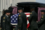 An honor guard from the 3rd Armored Cavalry Regiment places SSG Justin Vasquez' casket in a horse...
