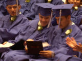 Graduates Cesar Deras (cq), left, and Javier Diaz (cq), center, look at Javier Davila Osorio's...