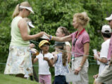 Hillary Lunke, left, winner of the 2003 U.S. Womens Open signs autographs just off the fourth...
