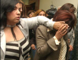 Brighton, Colo. -June 18,2004- April Garcia  gets help covering  her face after appearing in Adams...