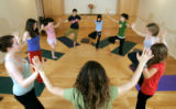 Yoga for Young Women instructor Shawna Suzyn (cq, center) leads a group tree pose at StudioBe Yoga...