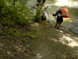 Gary Lacy (right) pulls his Kyake out of the Boulder Creek on Wednesday June 8, 2005 in Boulder,...