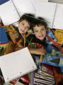 Twins Mitch, left, and Zach Finesilver, 9, under a pile of school supplies they're mom, Brenda has...