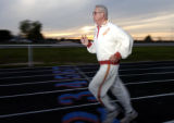 Wes Santee stands on the running track at Eureka, KS. wearing his original warm-up suite from when...