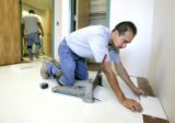 Antonio Rivera (rt) and Frank Meza (cq) lay new tile in a room in a barracks being renovated at...