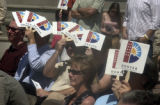Citizens shade themselves while listening to Denver Mayor John Hickenlooper deliver his third...