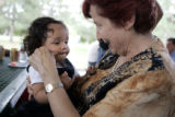 Marcelle Gallois pinches the cheeks of Ella Sainsot Stern, 11 months at Clement Park on Thursday,...
