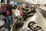 Denver, CO July 26, 2005 Passengers pick up their bags from one of the United luggage carousels at...