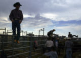 Stoney Zolman (cq),43,left, gets a better view of the  bull riding portion of the rodeo at the...