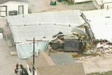 Police, lower left, move toward a bulldozer jammed into a warehouse attached to a Granby, Colo.,...