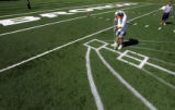 Denver Broncos Football Club's Brett Baird, cq, Assistant Turf Manager, paints a pass rush pattern...