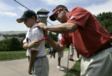 Chad Ribisi (cq), 9, of Colorado Springs, left, has his shirt signed by Rich Beem on the 1st hole...