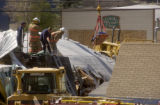 Granby, Colo., photo taken June 5, 2004- The body of Marvin Heemeyer is lowered by the aid of a...