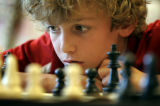 Neal Kornreich, 9, Boulder, cq, concentrates on his opponent's next move during a The Chess...