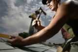 Total Discount Roofing employee Alberto Hernandez, cq, installs shingles on a home in Northglenn...