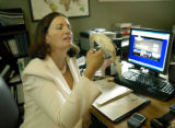 Denver, CO July 19, 2005 Michele Ashby, shown in her home office with Bob, one of her staff, just...